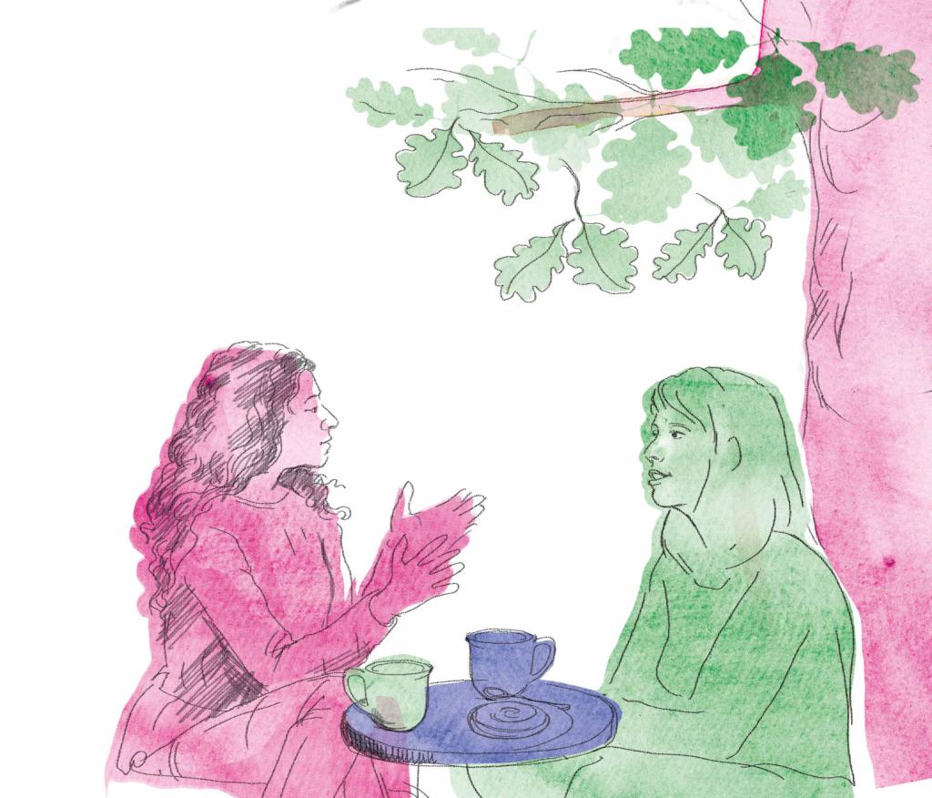 Två kvinnor sitter utomhus och har ett samtal